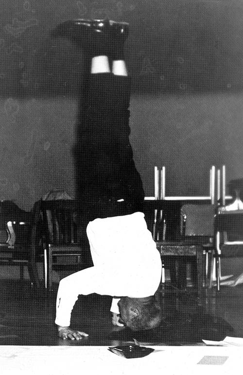 black and white photo of William Everitt doing a headstand