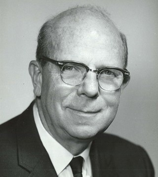black and white photo of William Everitt as a middle aged man with glasses wearing a suit.